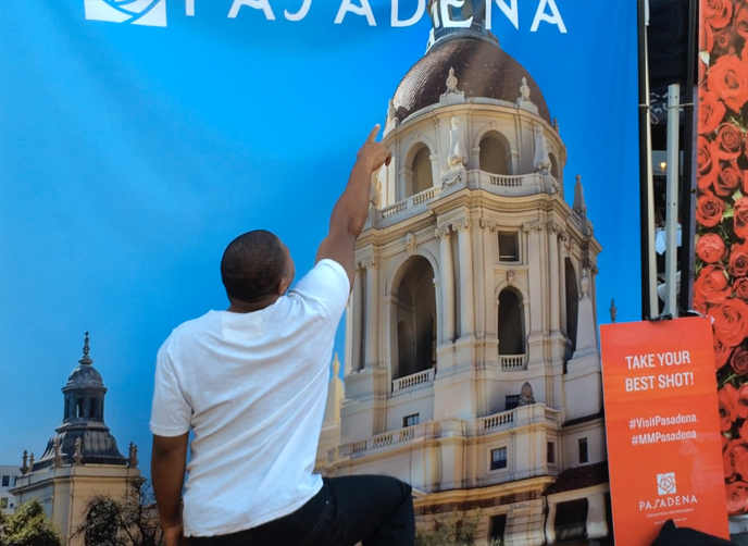 At the Make Music Pasadena 2015 photo banners, a man touches the dome of City Hall
