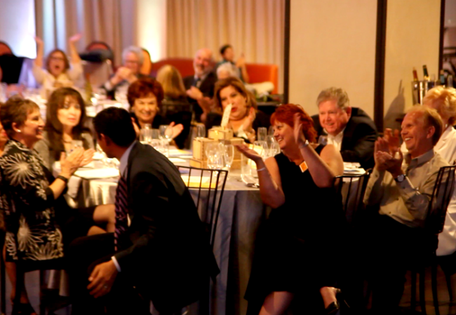 Audience at the Foothill Unity Center's 35th Birthday Gala cheering the winning bid